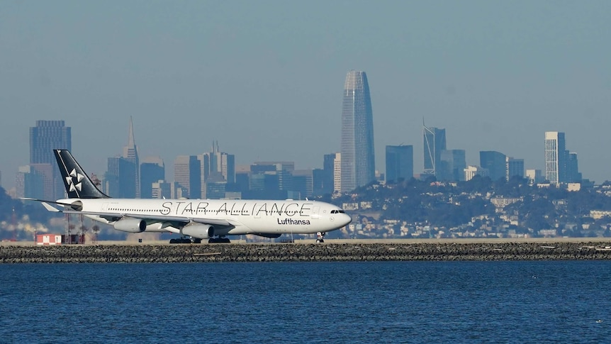 A passenger plane is seen sitting on a runway near a large body of water.