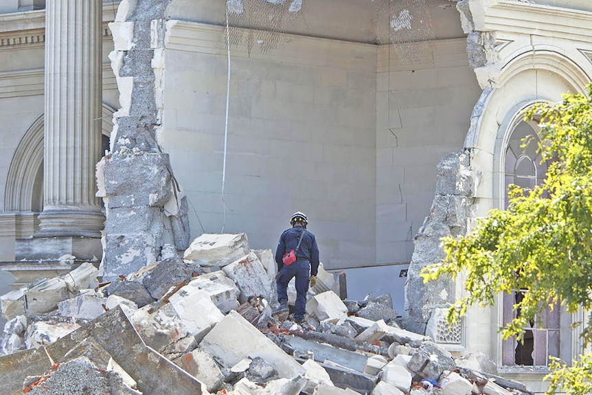 A rescue worker looks through the rubble after an earthquake of the Cathedral of Blessed Sacrament in Christchurch.
