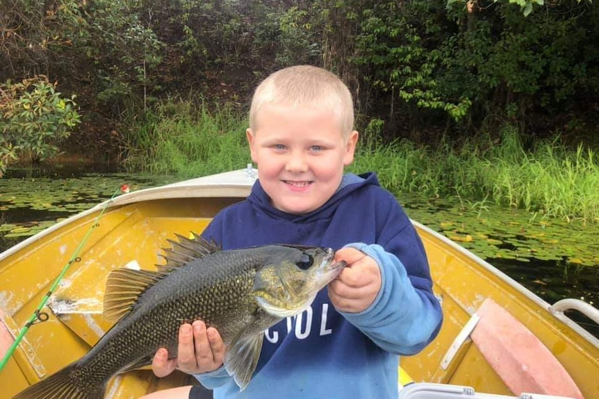 Young fisherman Fraser Prentice proudly holds a fish caught in the family's much loved tinny