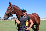 A young woman Mareeba Trainer standing outside with racehorse Regal Heart