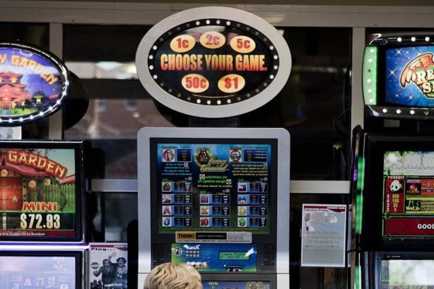 A woman plays a poker machine.