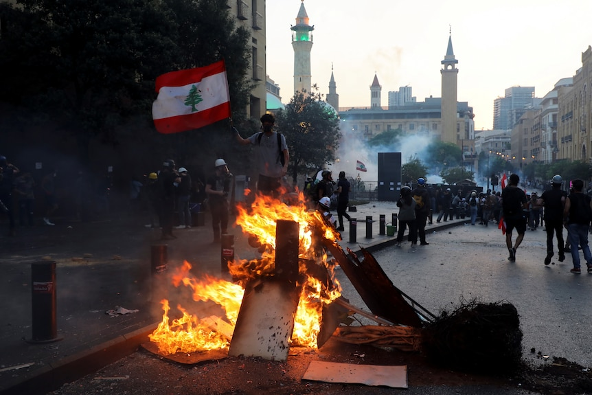 A man holds up a Lebanese flag near a fire as protesters march through the streets near parliament