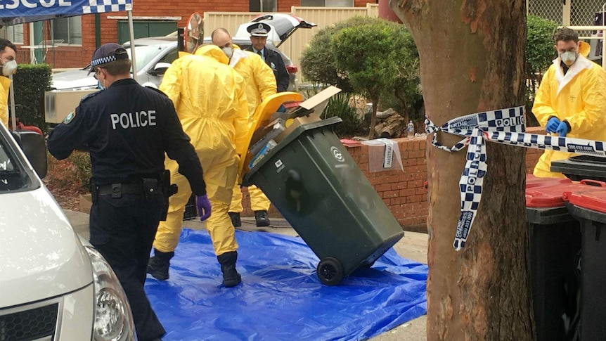 Counter-terrorism police, some dressed in yellow protective suits, outside a Lakemba property. One is dragging a bin away.