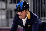 An Australian male competitor in the team equestrian eventing competition rides his horse over a hurdle.