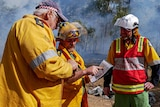 Three men in PPE gear look at a map while a fire burns behind them.