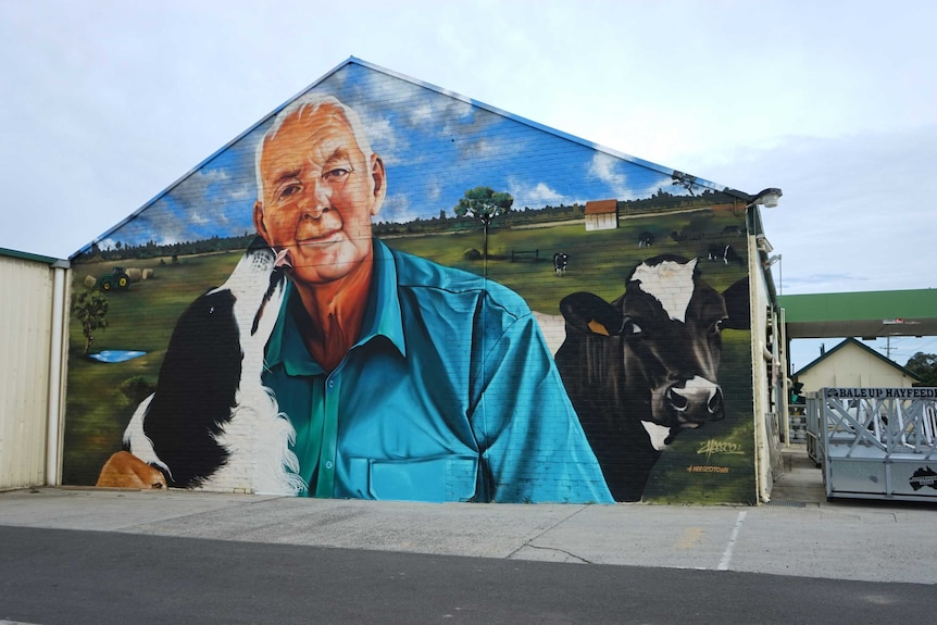 A mural showing a collie licking an older man's face.
