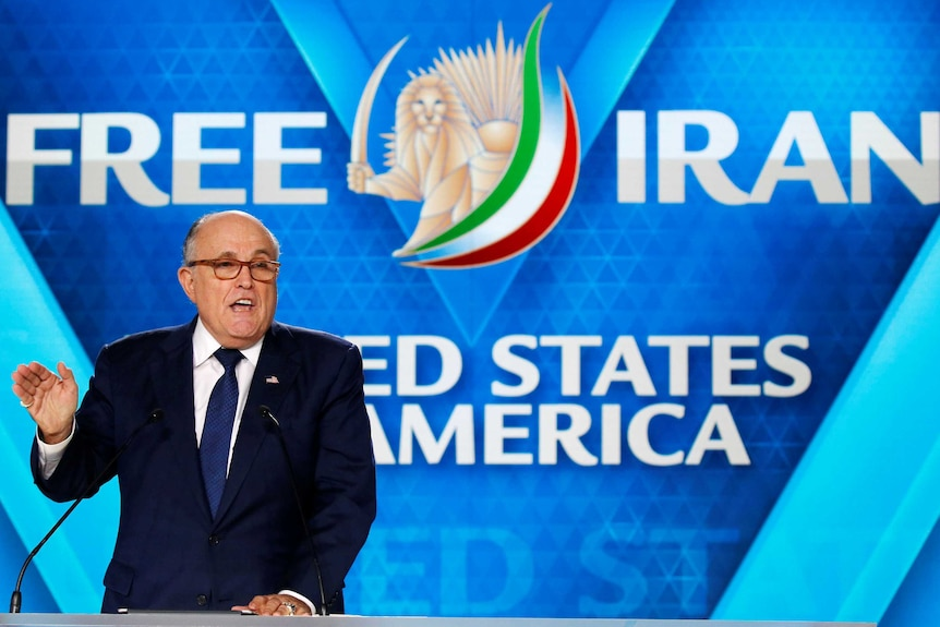 """Rudy Giuliani gestures while giving a speech, with """"Free Iran"""" written on screens in the background."""