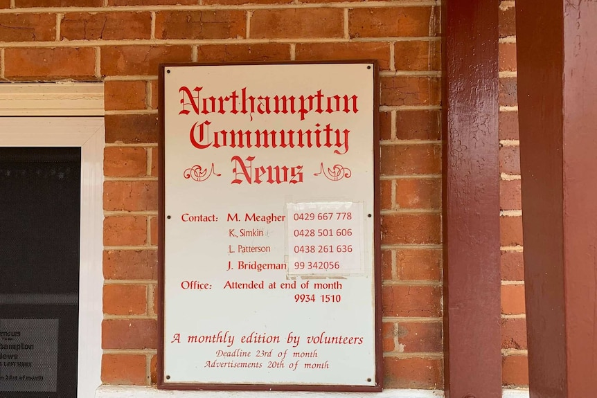 Sign on a red brick wall, in red writing 'Northampton Community News' with a list of names and phone numbers below.