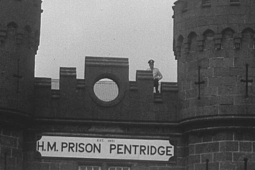 A historical black-and-white image of a prison guard looking over the gates of Victoria's Pentridge Prison.