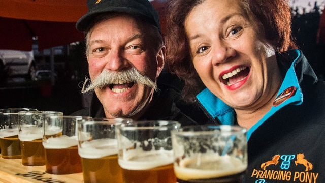A woman and a man smile over pints of beer.