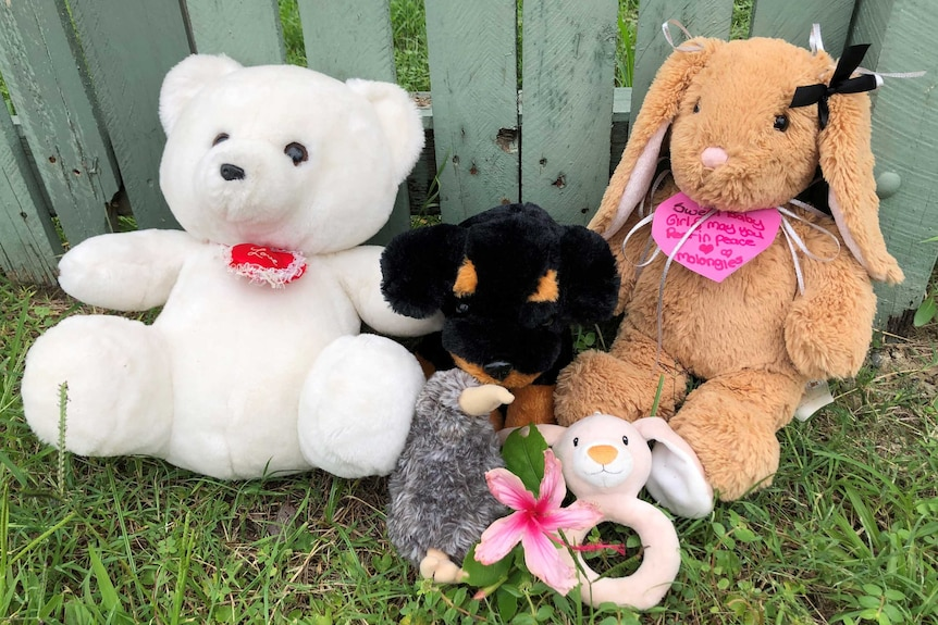 A teddy bear a stuffed bunny rabbit and a few other stuffed animals with cards sit along a fence