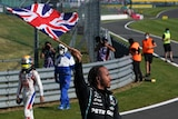 Driver holding a Union Jack flag celebrating with the crowd.