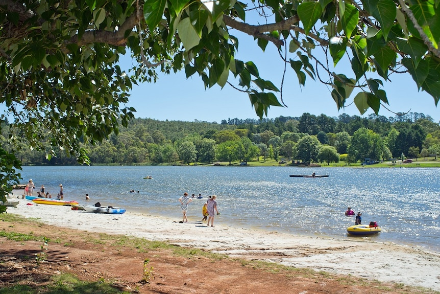 Families standing near and in the blue waters of Lake Canobolas, showing the beauty of rural New South Wales.