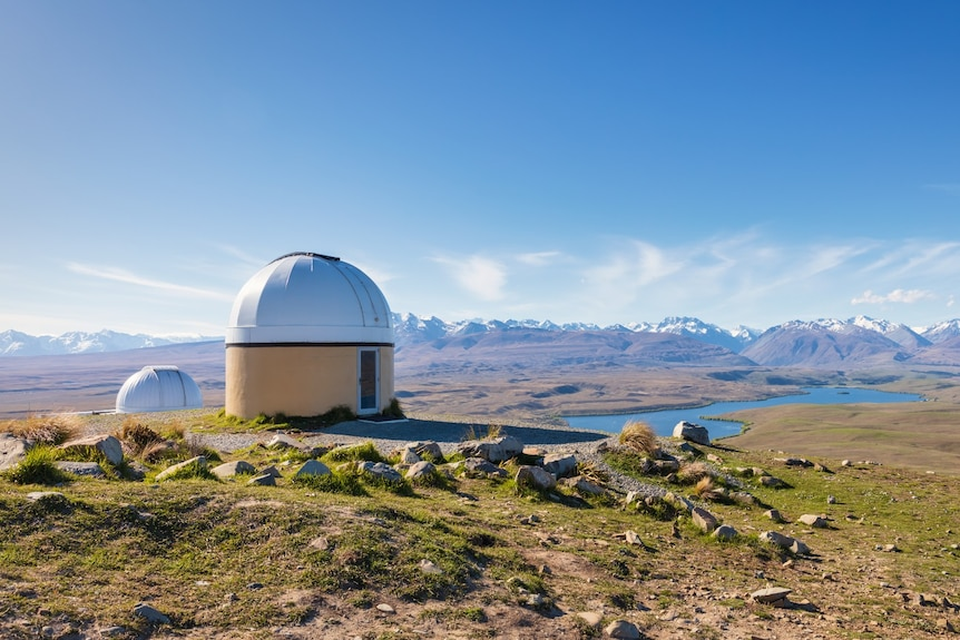 A dome atop a mountain and a lake below