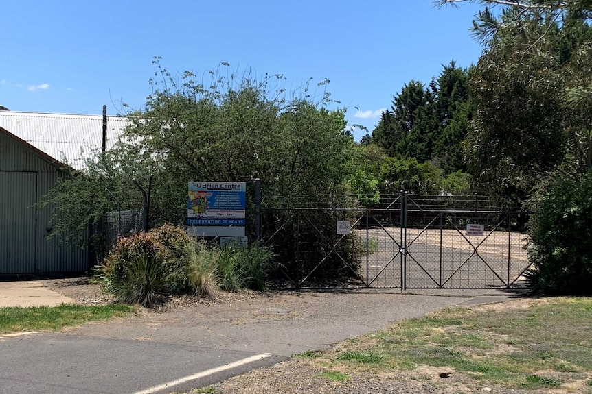 Exterior of a building, fence and sign with trees surrounding site