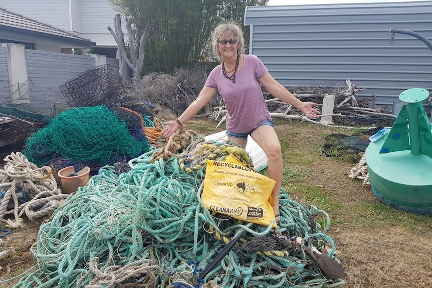Woman stands on top of a pile of fishing line, rope and other rubbish