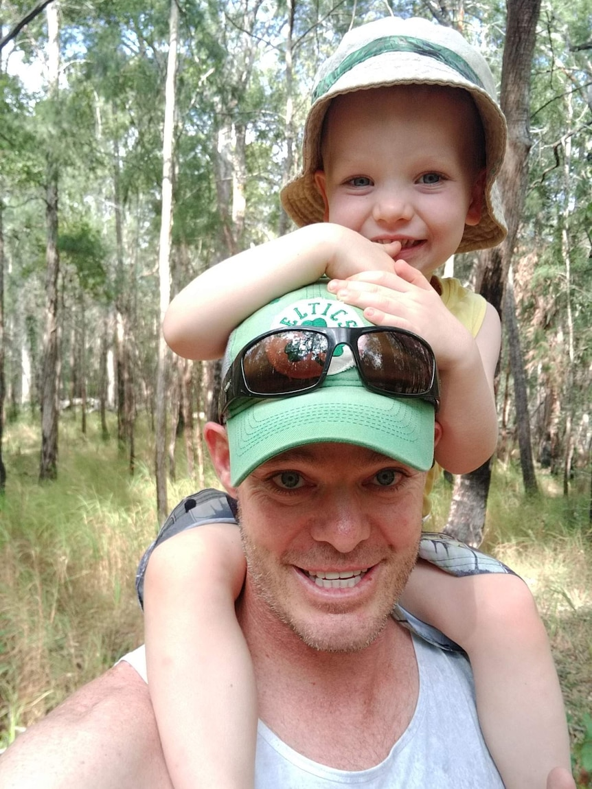 A photo of toddler Sonny on his dad's shoulders