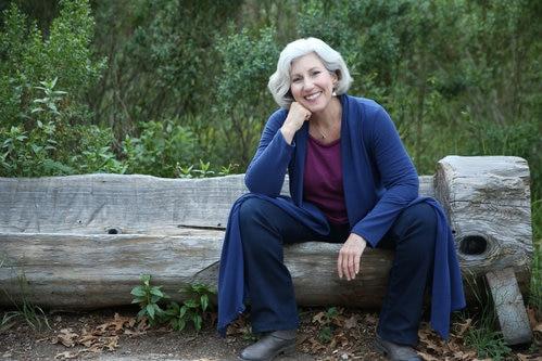 Ann Davidman sits on an outdoor log chair