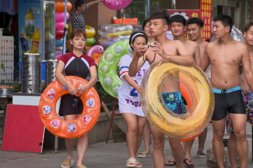 A group of young people with pool toys walking down a street