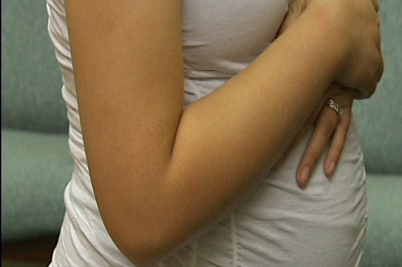 A pregnant woman stands with her hands wrapped across her stomach