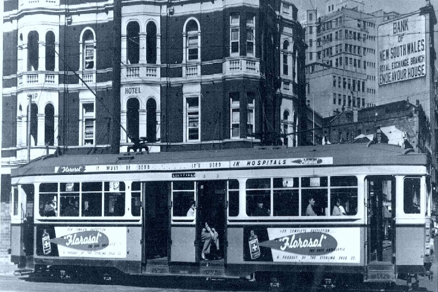 A black and white picture of a tram bearing a Florosol disinfectant ad in front of old buildings