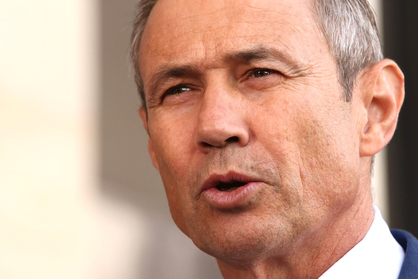 A close up of Roger Cook's face as he speaks at a media conference outside parliament