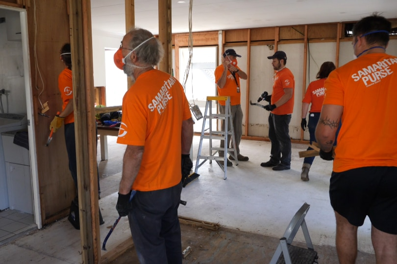 Six people working in orange Samaritan's t-shirts in a home stripped of interior wall sheeting bearing the wooden frame.