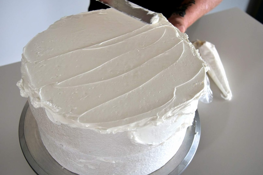 Close up photo of a woman's hands decorating a polystyrene block to look like a cake