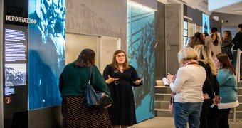 A historian explains a museum exhibit to guests.