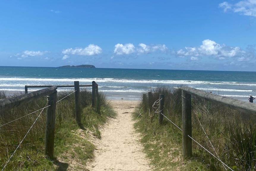 A sandy path leading to a beach.