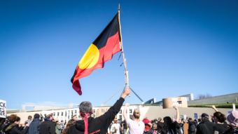 a person waves an indigenous flag in front of parliament house.