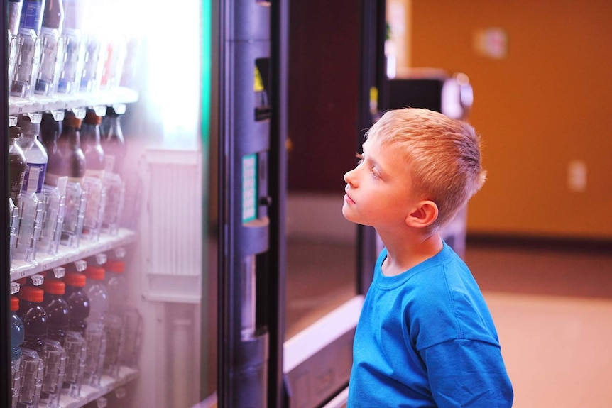 A a small blonde child looks longingly at a vending machine.