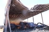 A hay shed warps as bales inside burn.