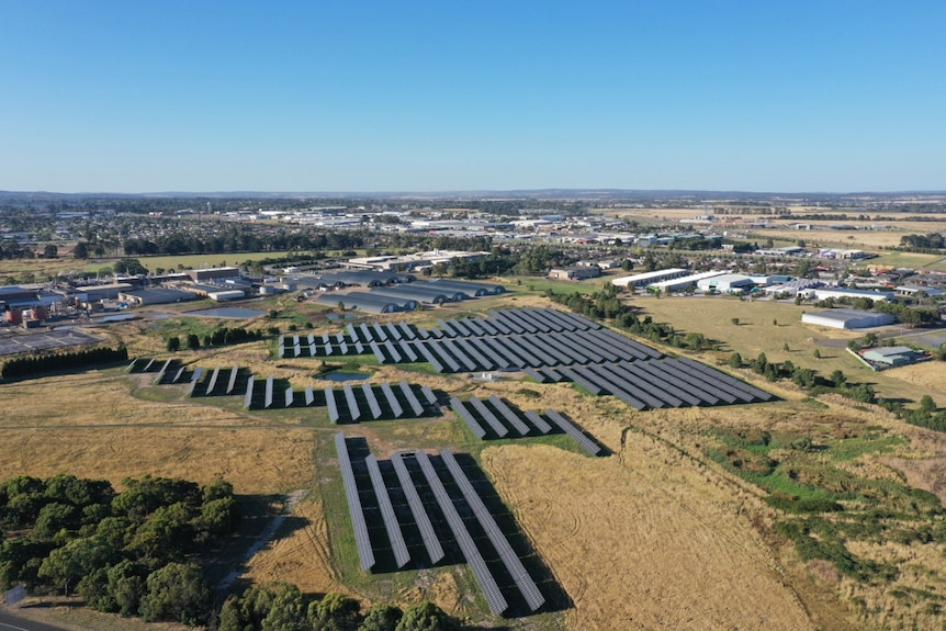 an aerial view of solar panels in open fields