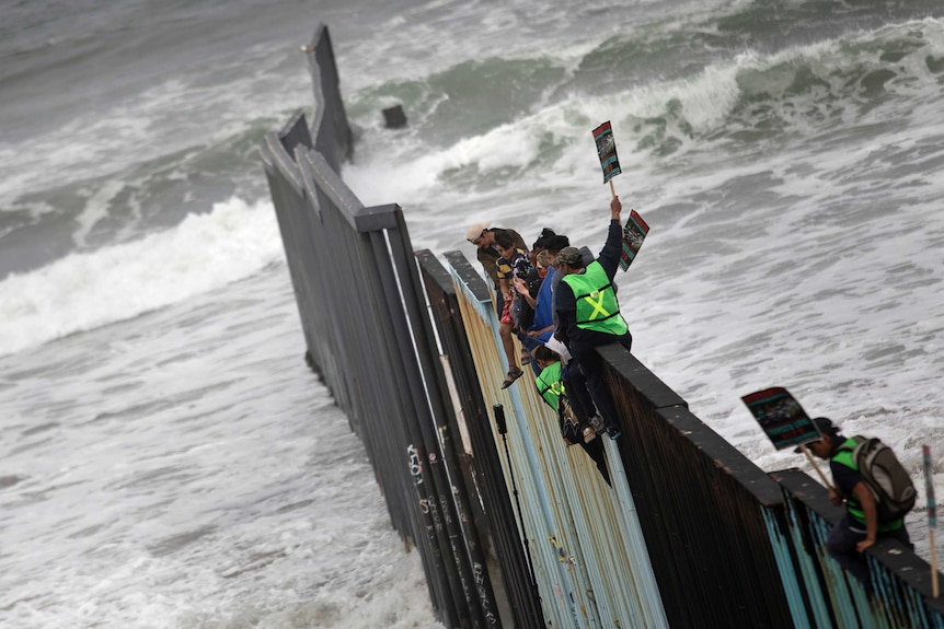 Migrants sit on top of the border wall on the beach, with waves crashing underneath them.