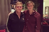 Sir Elton John and Tate Sheridan stand with their arms around each other