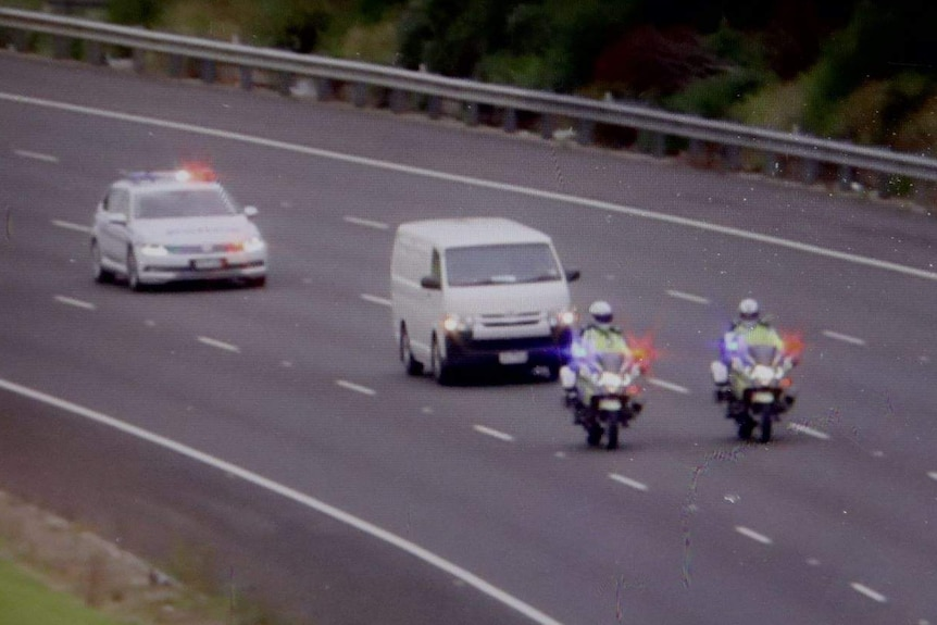 A white van being escorted by three police vehicles which include two officer's on motorcycles and a police car.