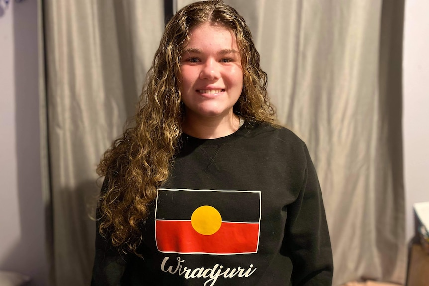 A teenager wearing a black jumper with the aboriginal flag