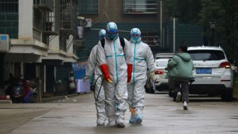 Workers from disease control and prevention department in protective suits disinfect a residential area in China.