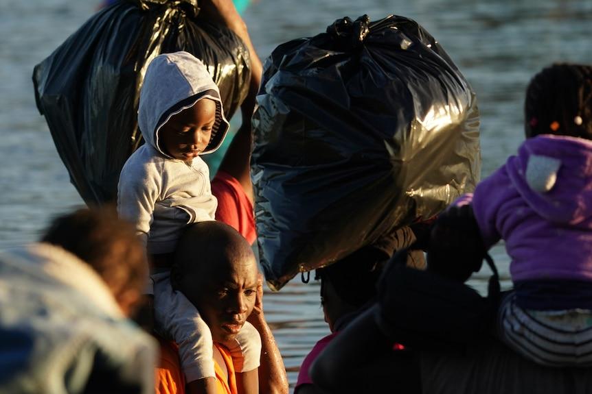 Un niño sosteniendo los hombros de un hombre mientras cruza un río.