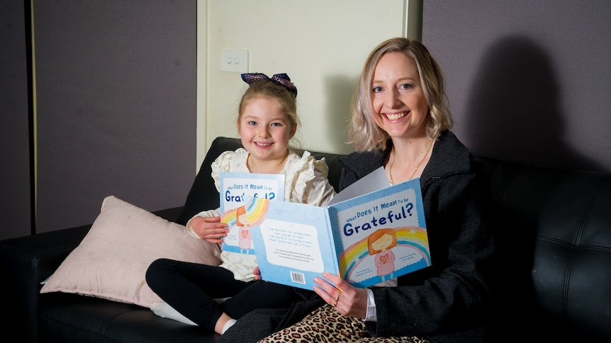 a woman and a girl sit on a couch reading a book together