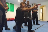 Acting Sgt James Tome demonstrates weapons handling procedures with a replica Glock pistol.