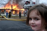 a young child turns her head to smile at the camera as a house burns down behind her.