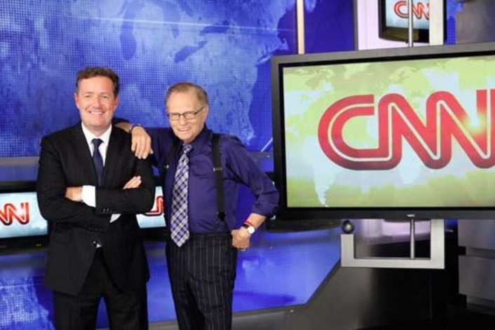 Piers Morgan and Larry King stand in front of a CNN logo.