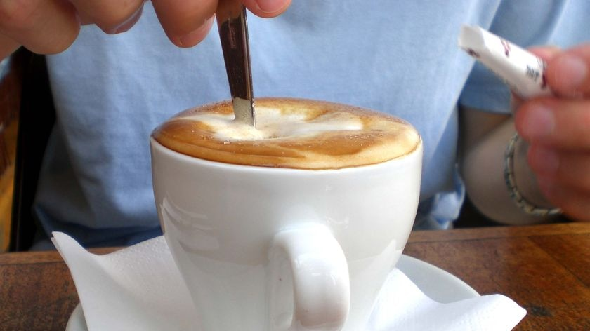 A person stirs their cup of coffee