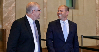 Scott Morrison and Josh Frydenberg smile as they walk in the foyer of Parliament House.