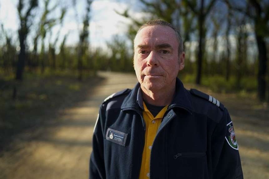 A man in uniform in front of burnt trees.