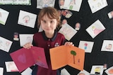 A young child in a school uniform holds up two coloured handmade cards