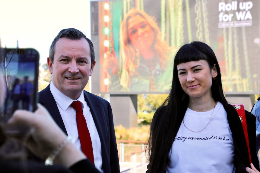 Someone takes a mobile photo of the Premier Mark McGowan and a woman with dark hair standing before a large video screen.