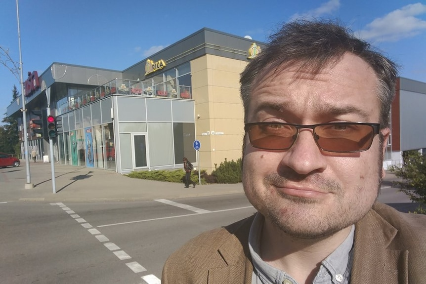 Selfie of journalist posing in front of shopping centre.